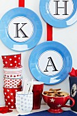 Blaue Teller als Wanddekoration mit Buchstaben beklebt, davor gemusterte Tassen