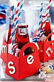 Bottles of soft drinks, napkins, drinking straws and sweets in small red paper bags decorated with letters