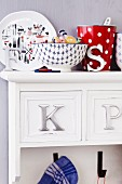 Crockery and tea towel hooks on kitchen cabinet with metal letters as drawer handles