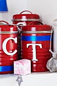Red storage containers decorated with metal letters