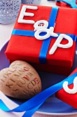 Ceramic letters on red gift box with blue ribbon and ceramic heart