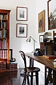 Thonet chair at simple wooden table, retro chrome table lamp and bookcase in study
