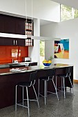 Stainless steel pendant lamps above counter with dark brown base units and bar stools