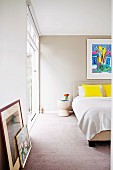 Double bed, splashes of colour provided by yellow scatter cushions and framed pictures leaning against wall in modern bedroom painted pale grey