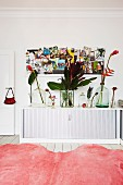 View across pink fur rug to white sideboard with roller doors and glass vases of tropical flowers below pin board on wall