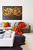 Low white coffee table on animal-skin rug, orange blanket and retro-style scatter cushions on sofa below modern painting on white wall