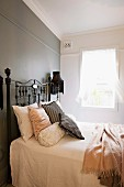 French bed with antique metal frame against grey-painted wall in simple bedroom with vintage ambiance