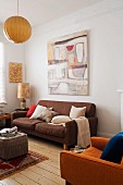 Retro sofa below picture on wall and comfortable sofa set on rustic wooden floor in living room in earthy shades