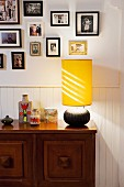 Table lamp with yellow fabric lampshade on wooden sideboard against white wainscoting and below framed photos