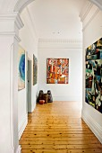 Spacious hallway in period building with wooden floor and modern artworks on walls with stucco elements