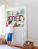 Kind vor einem mit nostalgischen Büchern und dem Namenszug FRED dekorierten Regal im Kinderzimmer
