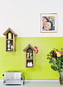 Bird-box-shaped spice racks on green-painted kitchen wall