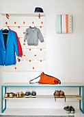 Coat rack with neon orange accents, fuse box covered in fabric and bench spray-painted blue
