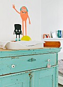 Rustic baby-changing cabinet with peeling turquoise paint and comic characters painted on wall
