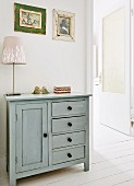 Table lamp on rustic cabinet painted pale grey next to open door in foyer