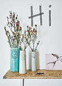 Danish designer vases on DIY chipboard shelf below greeting written in washi tape on wall