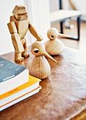 Holzfiguren (Gorillamotiv und Vogelmotiv) auf dem abgewetzten Leder eines alten Turnkastens