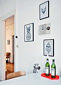 Red, designer tray and vintage mincer on kitchen table, pictures and clock on wall and view into hallway of period apartment