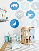 Designer cot made from pale wooden rods with canopy against wall with animals motifs in circles of colour