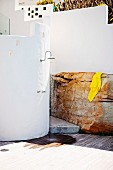 Outdoor shower on curved, white wall next to yellow towel on boulder