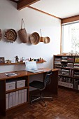 Home office in corner with collection of baskets hanging on wall
