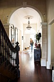 View from stairwell through archway of woman and dog in narrow hallway in grand villa