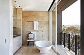 Free-standing bathtub next to open, sliding balcony door in modern bathroom with sand-coloured tiles on walls and floor