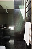 Black-tiled bathroom with shower area behind glass partition
