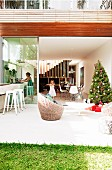 Christmas tree on sunny terrace in front of open, sliding glass door and view of family in interior