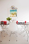 Classic, white shell chairs around glass table with red glasses in minimalist dining room