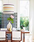 Vase mit tropischer Blume auf Esstisch und Stühle mit weisser gepolsterter Rückenlehne unter Hängeleuchte mit gestreiften Schirm