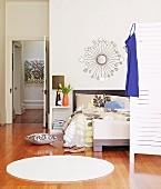 Round, white rug on parquet floor in modern bedroom; open door with view into hallway in background