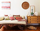Daybed with pale cushions and colourful scatter cushions on wooden frame next to chest of drawers against white, wooden wall