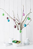 Still-life arrangement of crockery and glossy Easter eggs hanging from twigs