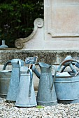 Old zinc jugs with price labels on a gravel surface in front of an antique wall