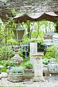 Zum Verkauf angebotene Steintöpfe und Säulen im Antikstil auf einer Kiesfläche im Garten; Laterne und weisse Metallstühle im Hintergrund