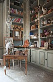 A built-in cupboard filled with antique living accessories for sale in an old French country house