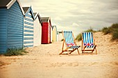 Colourful beach huts & two deckchairs on beach (Sussex, England)