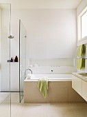 Pale bathroom with niche above bathtub and floating washstand; floor-level shower behind glass screen to one side