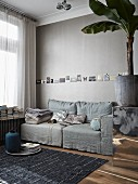 Living room in warm shades of grey with row of postcards tacked on wall above comfortable sofa