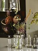 Single flowers in old glass bottles on dining table below pendant lamp with glass lampshade