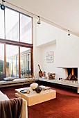 Seating area in front of fireplace with cubic wooden table on rust red carpet, encircling concrete bench and sofa in room with double-height glass facade
