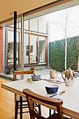 Dining table set for breakfast with modern, blue and white crockery and wooden chairs in front of glass wall with view into courtyard and facade forming a right angle