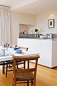Table set for breakfast and simple wooden chairs in front of island counter in purist, white, designer kitchen
