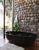 Designer bathroom with black, free-standing tub against stone wall and glass wall with view of garden terrace