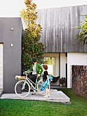 Mother on bike and son with skateboard in front of contemporary beach house in Queensland