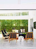 60s armchairs and sofa on terrazzo floor in bright interior; view of bamboo hedge and screen through wide, sliding glass wall