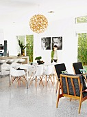 Open-plan interior in Australian beach house with 60s retro armchairs, classic shell chairs in dining area and concrete breakfast bar; black and white portraits of children