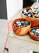 Lego pieces in wooden bowls on corner of concrete kitchen counter