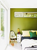 Cylindrical chest of drawers and classic chair for hanging clothes next to double bed; transom window with view of bamboo hedge in green-pained wall